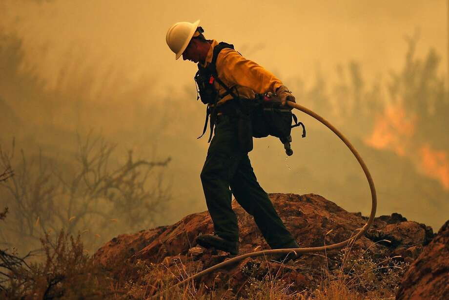 A firefighter battles the Mills Canyon Fire near Entiat in Chelan County, Wash., on July 10 as hot, dry weather blankets the state and has fire crews ready for action.  Photo: Bettina Hansen, McClatchy-Tribune News Service