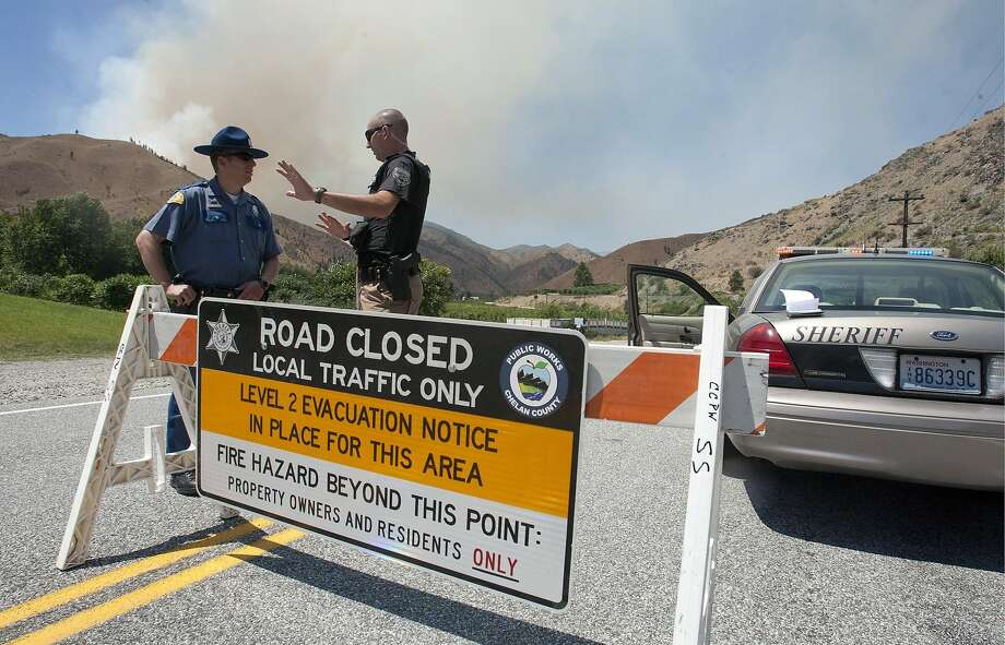 In this photo taken on Tuesday, Aporil 8, 2014, Washington State Patrol Trooper Brian Moore, left and Chelan County Sheriff department Deputy Jeremy Mannin talk about who is allowed past the road block on the Entiat River Road near the intersection with Mills Canyon as a wildfire burns in Entiat, Wash. Photo: Mike Bonnicksen, Associated Press