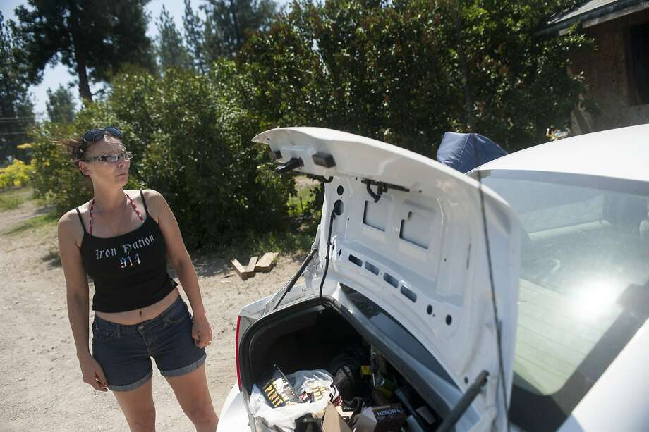 Lisa Sheppard stands next to the packed trunk of her car as she looks to the hills behind her home as fire crews work to contain the 900-Acre Lake Spokane Fire on Thursday, July 10, 2014, near Ford, Wash. Sheppard who has lived off of Highway 291 for years said this was not the first fire she has seen burn through the countryside near her home. Photo: Tyler Tjomsland, Associated Press