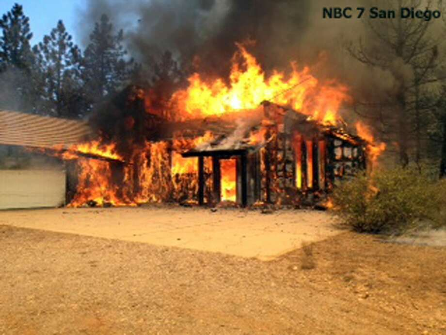 In this still frame from video provided by KNSD-TV, a home is fully involved in flames as crews scrambled to corral a wildfire that burned two homes near the San Diego County mountain town of Julian in Southern California Thursday, July 3, 2014. The blaze erupted around 10:30 a.m. and prompted the mandatory evacuation of 200 homes. Firefighters attacked the 150-acre blaze in the air and on the ground. The fire destroyed two homes and an outbuilding and was 15 percent contained at nightfall, state fire Capt. Kendal Bortisser said.  Photo: Associated Press