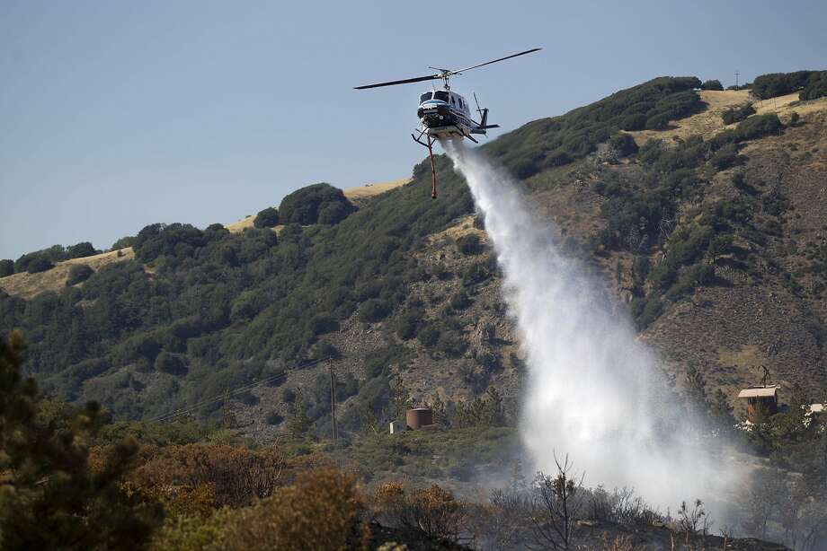 A firefighting helicopter drops a load of water on part of the Banner Fire in the mountain town of Julian, Calif., on Thursday, July 3, 2014.  Photo: Sean M. Haffey, Associated Press