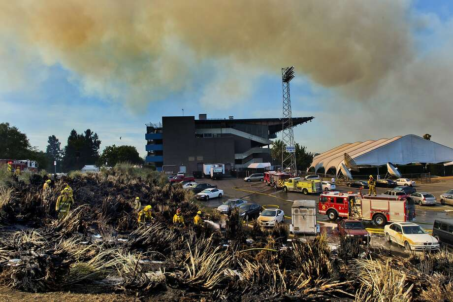 Smoke billows as Sacramento firefighters contain a blaze that jumped Levee road near the race track at California State Fairgrounds Saturday, July 4, 2014 in Sacramento, Calif. A wildfire that broke out near the Cal Expo fairgrounds in Sacramento forced the evacuation of a water park and the cancellation of a minor league soccer game. But the fire didn't stop the fireworks.  Photo: Renee C. Byer, Associated Press