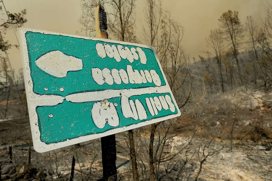 A sign, melted in the intense heat of the Butts Fire, gives arrows for Snell Valley Road and Berryessa Estates, Wednesday, July 2, 2014, near Middletown Calif. By early evening, the Butts Fire in remote Pope Valley grew to 3,800 acres from 3,200 acres, said Daniel Berlant, a spokesman for the California Department of Forestry and Fire Protection. The blaze is not threatening any major vineyards, Berlant and a spokeswoman for a vintners association said. Photo: Kent Porter, Associated Press