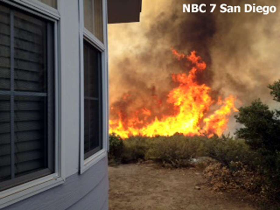 In this still frame from video provided by KNSD-TV, flames near a home as crews scrambled to corral a wildfire that burned two homes near the San Diego County mountain town of Julian in Southern California Thursday, July 3, 2014. The blaze erupted around 10:30 a.m. and prompted the mandatory evacuation of 200 homes. Firefighters attacked the 150-acre blaze in the air and on the ground. The fire destroyed two homes and an outbuilding and was 15 percent contained at nightfall, state fire Capt. Kendal Bortisser said. (AP Photo/KNSD-TV) Photo: Associated Press