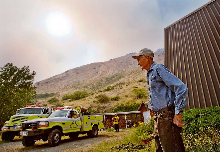 Les Kile watches as a Chelan County fire crew arrives at his house near Entiat, Wash., Wednesday afternoon, July 9, 2014. He was put on a level three evacuation order. He and his wife decided to stay at their home at the mouth of Spencer Canyon even though fire had crested the mountain overlooking their home. Fire spokesman Mick Mueller says about 250 firefighters were aided by air tankers dropping retardant and helicopters dropping water Wednesday on the Mills Canyon fire. Several dozen homeowners have been warned they might need to evacuate.  Photo: Don Seabrook, Associated Press