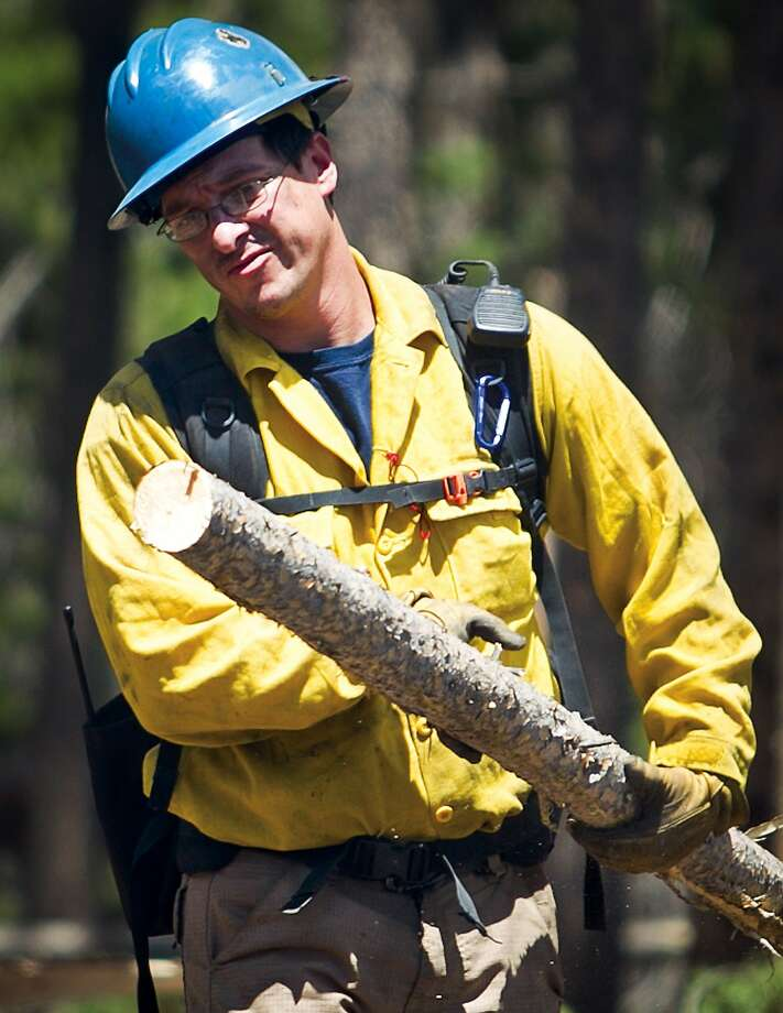 Natrona County firefighter Max Borino clears pieces of fallen timber from a bulldozer path Wednesday, July 9, 2014, around the fire containment perimeter near Lake Owen in the Medicine Bow National Forest, west of Laramie, Wyo. Photo: Jeremy Martin, Associated Press
