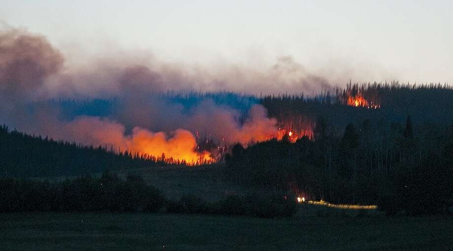 In this photo taken on Monday, July 7, 2014, a truck takes the road from Lake Owen as a wildfire burns in the background at Medicine Bow National Forest west of Laramie, Wyo. Fire managers said Tuesday they ordered two heavy air tankers and three helicopters. Forty firefighters were on the scene. Photo: Chilton Tippin, Associated Press