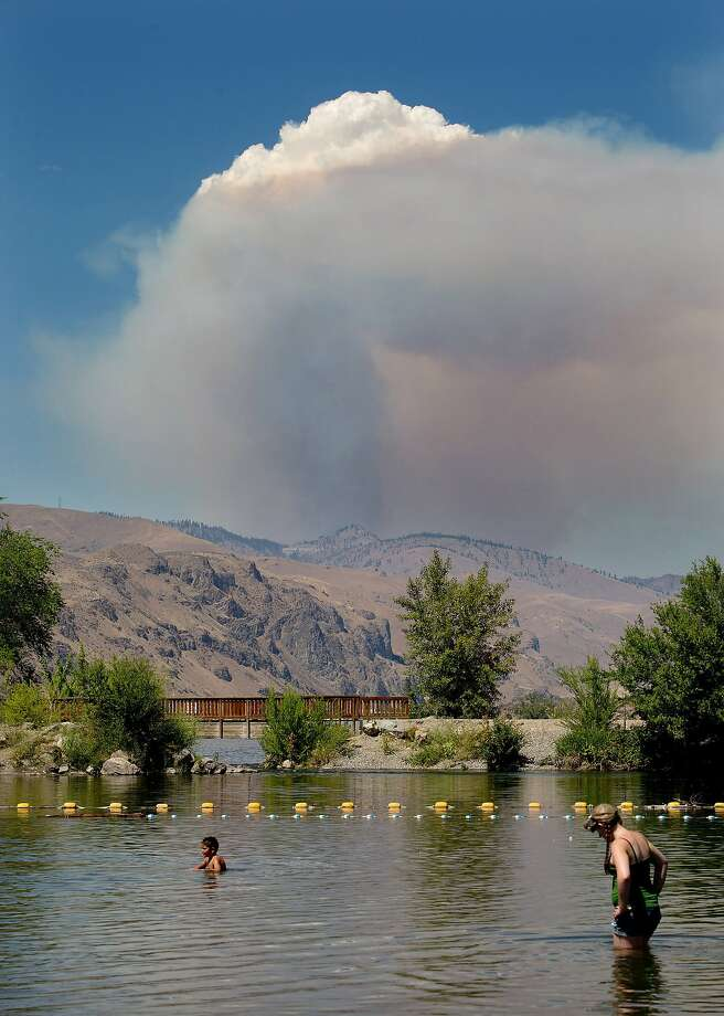 A plume of smoke and steam rises from the Mills Canyon Fire near Entiat, Wash., on Tuesday, July 8, 2014, as seen from Walla Walla Point Park and the Columbia Rive in Wenatchee. The fire is at 200 acres and growing according to Chelan County Emergency Management. Photo: Don Seabrook, Associated Press
