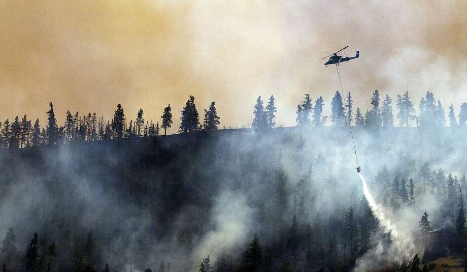 In this photo taken on Tuesday, July 8, 2014, a helicopter drops water on a wildfire on a hillside alongside the Entiat River Road, just up canyon from the intersection with Mills Canyon in Entiat, Wash.  Photo: Mike Bonnicksen, Associated Press