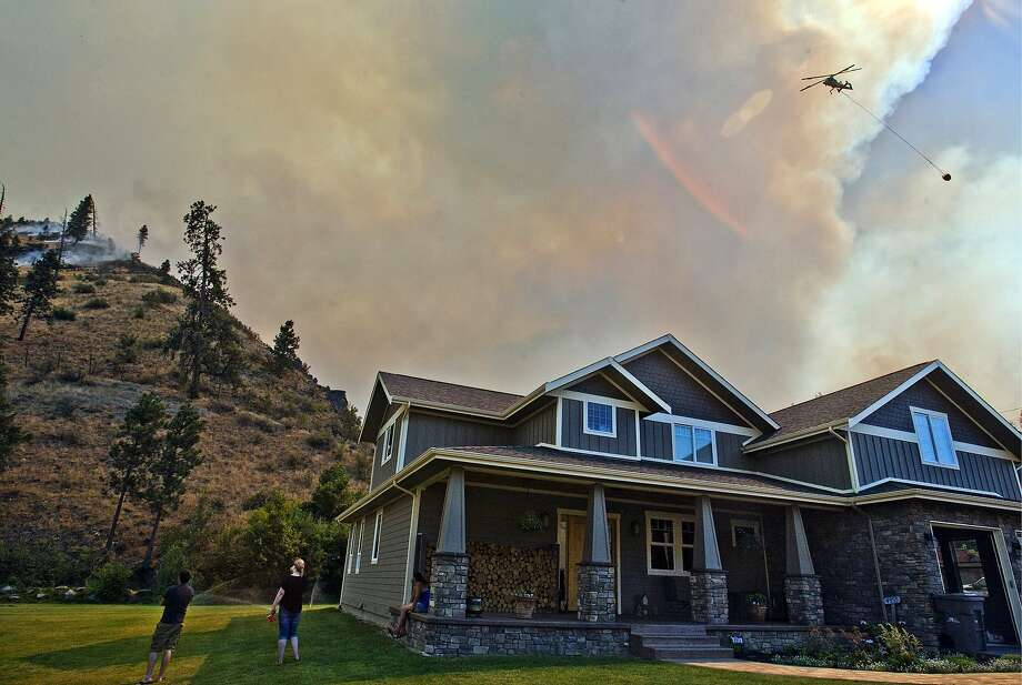 A homeowner and friend watch as helicopters put water on the Mills Canyon wildefire behind their near Entiat, Wash. Photo: Mike Bonnicksen, Associated Press