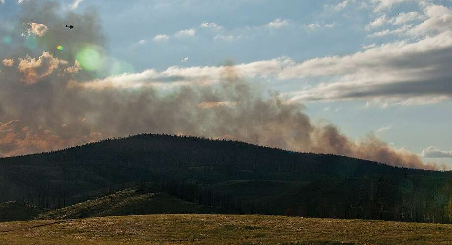 In this photo taken on Monday, July 7, 2014, a plane flies through the smoke of a wildfire, which began north of Lake Owen in Medicine Bow National Forest west of Laramie, Wyo. Fire managers said Tuesday they ordered two heavy air tankers and three helicopters. Forty firefighters were on the scene. Photo: Chilton Tippin, Associated Press