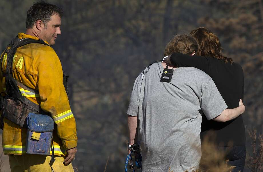 Anne Elizabeth, whose house was spared in a wildfire, hugs friend Maria Simas as Paul Thomas, volunteer firefighter with the Julian/Cuyamaca Fire Protection Service, looks on, Thursday, July 3, 2014, in the Julian, Calif, area.  Photo: Sean M. Haffey, Associated Press
