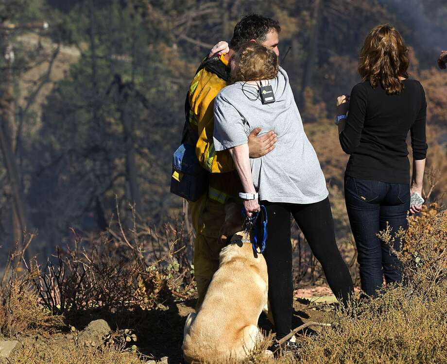 Anne Elizabeth, whose house was spared in a wildfire, hugs Paul Thomas, volunteer firefighter with the Julian/Cuyamaca Fire Protection Service, on Thursday, July 3, 2014, in the Julian, Calif, area.  Photo: Sean M. Haffey, Associated Press