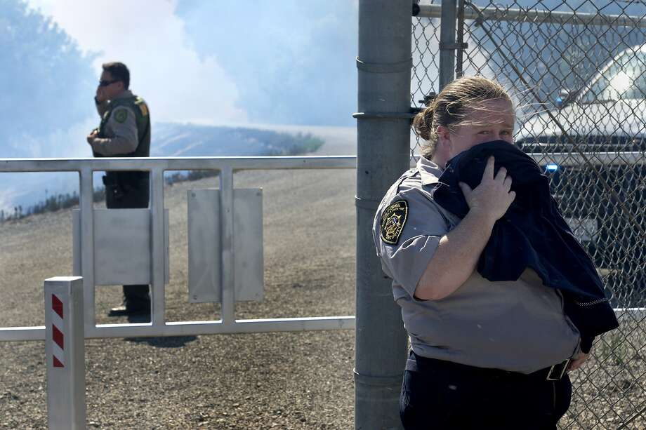 Cherri Seely, right, a California Expo State Fair Security guard covers her face as she keeps watch on Levee Road near the Race Track at Cal Expo as a grass fire burns Saturday, July 4, 2014 in Sacramento, Calif. A wildfire that broke out near the Cal Expo fairgrounds in Sacramento forced the evacuation of a water park and the cancellation of a minor league soccer game. But the fire didn't stop the fireworks. Photo: Renee C. Byer, Associated Press
