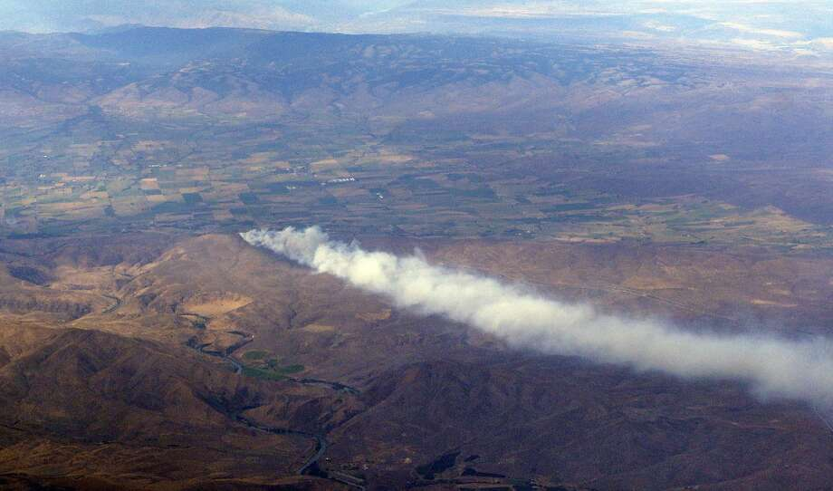 In this aerial photo, smoke billows from a wildfire in the Manastash Ridge area of central Washington Thursday, July 3, 2014, near Ellensburg, Wash. The blaze was reported about Thursday afternoon and has so far burned across about 2,000 acres of sagebrush, temporarily closing a nearby eastbound section of Interstate 82. Jim Duck, at the Central Washington Interagency Communications Center, said five helicopters were fighting the fire with help from several bulldozers and several dozen firefighters and said that no homes are threatened.  Photo: Rachel La Corte, Associated Press