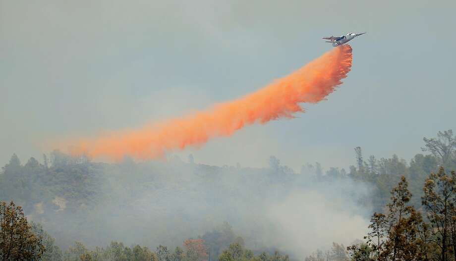 A Cal Fire air tanker drops retardant on a spot fire off the main Butts Fire, Wednesday, July 2, 2014, in Napa County, Calif. Photo: Kent Porter, Associated Press
