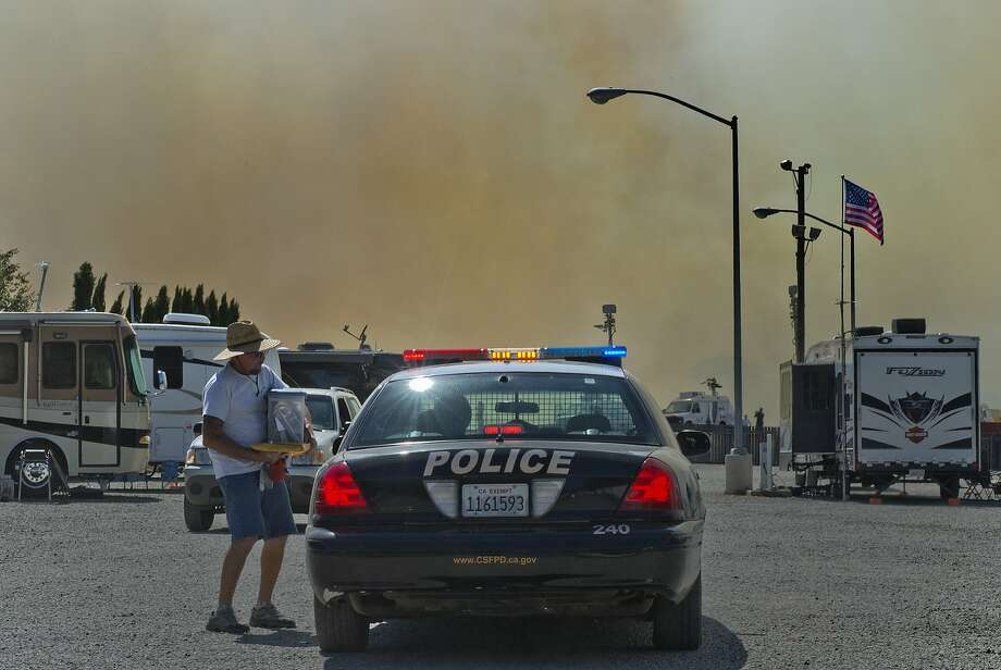 A man holding his possessions leaves the mobile camp  grounds at Cal Expo after chatting with a police officer at the scene as a wildfire burns Saturday, July 4, 2014 in Sacramento, Calif. A wildfire that broke out near the Cal Expo fairgrounds in Sacramento forced the evacuation of a water park and the cancellation of a minor league soccer game. But the fire didn't stop the fireworks.  Photo: Renee C. Byer, Associated Press