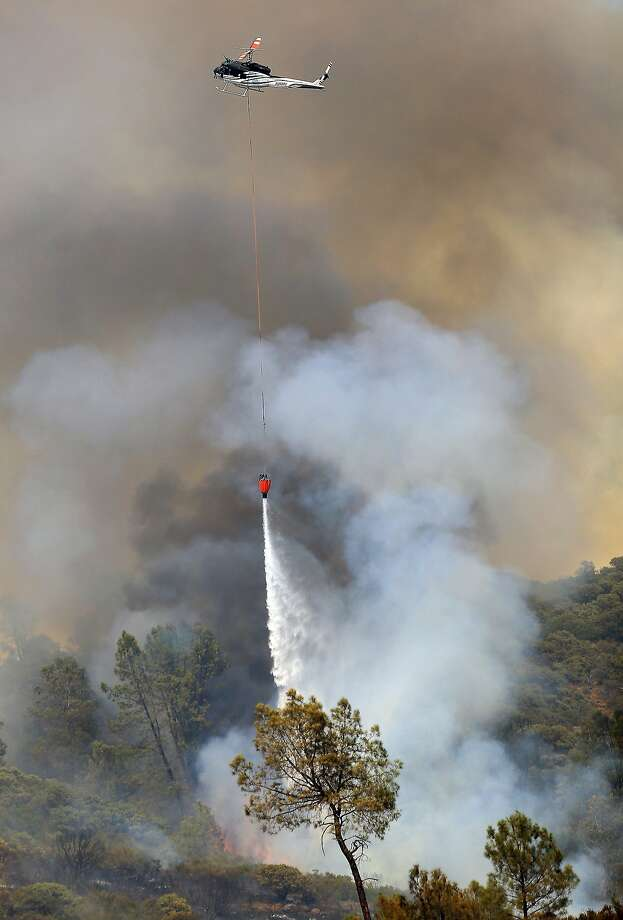 A private hire helicopter makes water drop on the Butts Fire above Butts Canyon Road as the afternoon winds kicked up, Wednesday, July 2, 2014, near Pope Valley in Napa County, Calif.  Photo: Kent Porter, Associated Press
