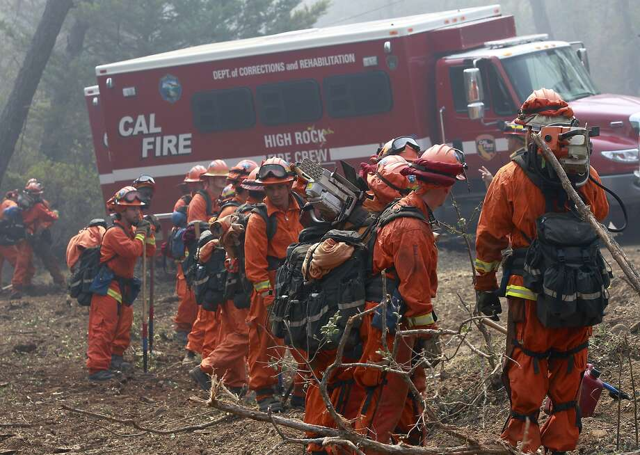 A Department of Corrections hand crew mobilizes to cut a containment line off of Butts Canyon Road near Middletown, Calif., on Wednesday, July 2, 2014. A raging wildfire in rural Northern California has spread over 5 square miles and forced the evacuation of 200 homes in Napa County, but was not threatening any major vineyards on Wednesday, a fire official and a spokeswoman for a vintners association said.  Photo: Paul Chinn, Associated Press
