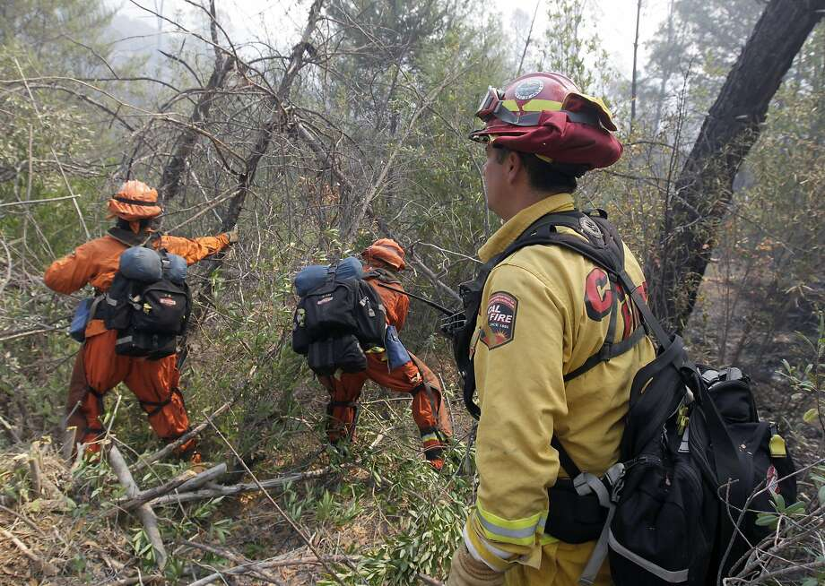 A Cal Fire supervisor directs a Department of Corrections hand crew cutting a containment line near Middletown, Calif., on Wednesday, July 2, 2014. A raging wildfire in rural Northern California has spread over 5 square miles and forced the evacuation of 200 homes in Napa County.  Photo: Paul Chinn, Associated Press