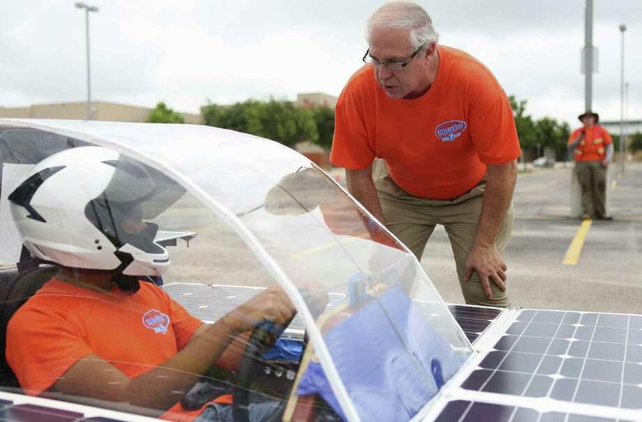 Ricardo Sanchez, 17, of Madison High School  listens to teacher Joe Dungan's instructions between test runs of the solar car Helios 2. Photo: Timothy Tai / San Antonio Express-News / © 2014 San Antonio Express-News