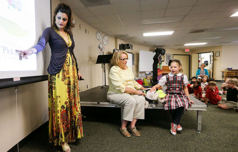 """Six-year-old Allison Williams, seated right, reads from the screen as """"Miss Nikki, the Literature Lady,"""" left, and Readmore the Dog read with students at Concordia Lutheran School May 20. Photo: Marvin Pfeiffer / Alamo Heights Weekly / EN Communities 2014"""