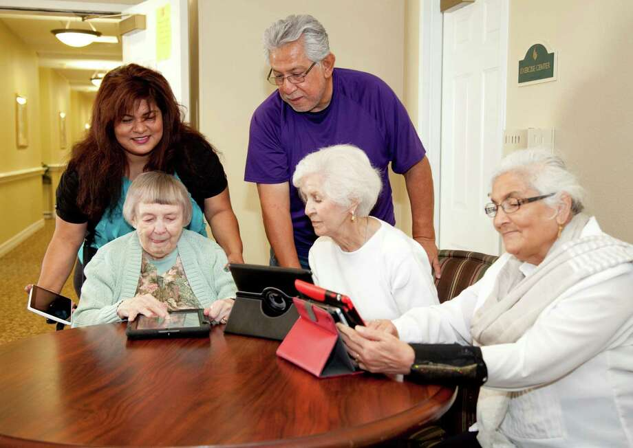 The Abbey at Westminster Plaza activity director Veronica Ramirez and caregiver Rudy Medina assist residents Mary Lundblad, Mary L. Cobb and Najma Nizami in a recent iPad instruction class.