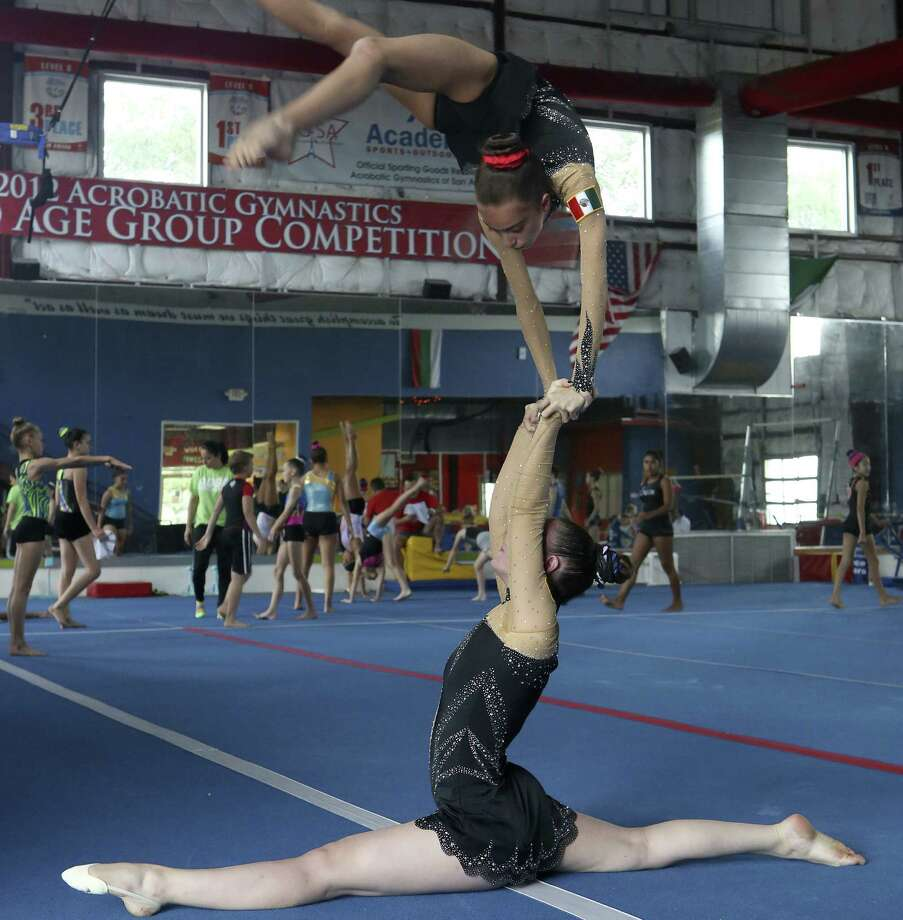 Ani Caballero, 17, bottom, is a strong rock as her partner, Isabella Melendez, 13, leaps into position during practice at Flip City. They're from the United States, but the two girls comprise Team México in acrobatic gymnastics competition. They have won 15 medals at all levels of competition. Photo: Photos By / ©2014 San Antonio Express-News