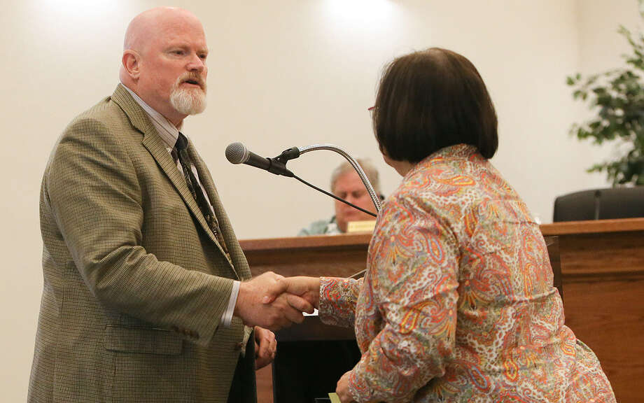 Tim Howell, left, shakes hands with City Secretary Janie Willman after Howell was sworn in as Castle Hills' mayor at a July 8 City Council meeting. Photo: Marvin Pfeiffer / Stone Oak Weekly / EN Communities 2014