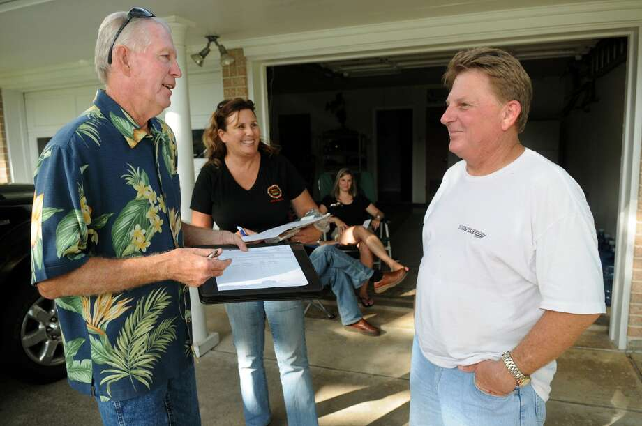 David Tague, left, and Laura Wilson, try to convince Tomball resident Billy Smith to sign their petition to change a city statue limiting liquor sales. Photo: Jerry Baker, Freelance
