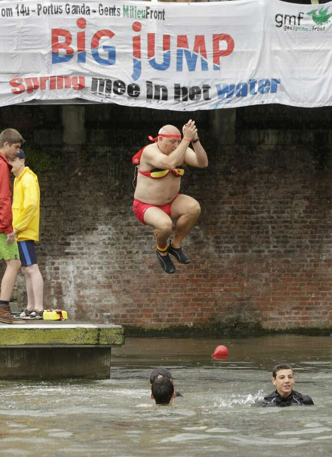 Some male bosoms require support:A bikini-wearing Belgian plunges into a canal in Ghent. Photo: Yves Logghe, Associated Press