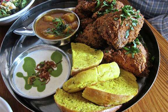 The Tuesday fried chicken special at Pondicheri is served thali-style with toasted pumpkin buns, fingerling potato curry and yogurt raita swirled with green chutney.