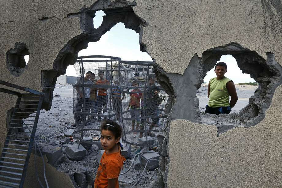 Suma Abu Mahsen, 7, stands by a damaged wall of a house hit by an Israeli missile in southern Gaza. Photo: Lefteris Pitarakis, Associated Press