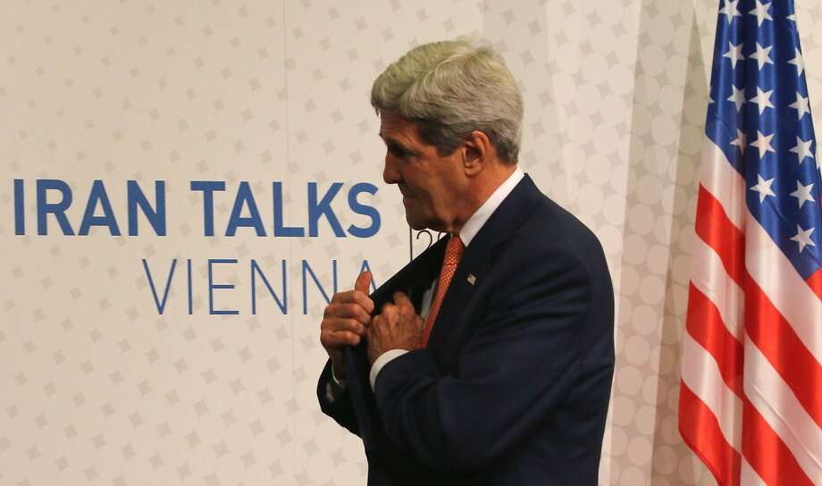 U.S. Secretary of State John Kerry leaves a press conference after closed-door nuclear talks on Iran in Vienna, Austria, Tuesday, July 15, 2014.  Intense negotiations with Iran have yielded ?tangible progress,? U.S. Secretary of State John Kerry said Tuesday, but significant gaps remain ahead of a July 20 target date for a deal meant to put firm curbs on Tehran's nuclear activities in exchange for an end to sanctions. (AP Photo/Ronald Zak) Photo: Ronald Zak, Associated Press
