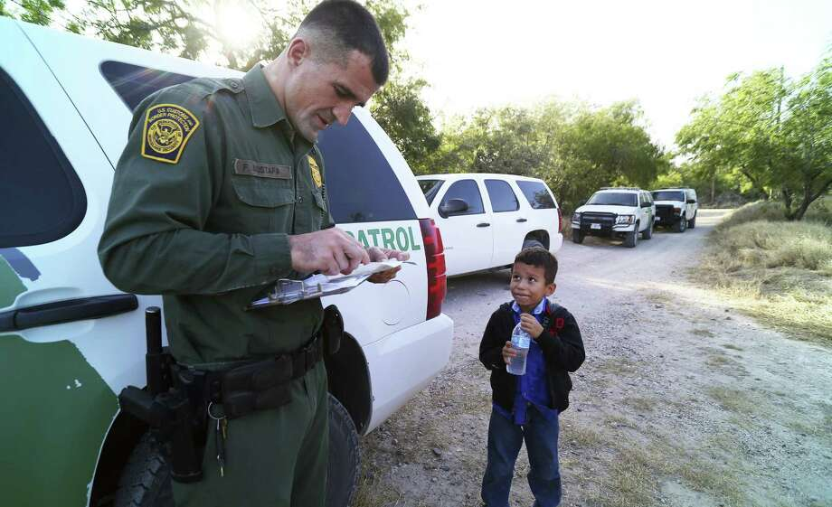 A Border Patrol agent reads the birth certificate of Alejandro, 8. A group of civilians plans to patrol the border with guns. Photo: Jennifer Whitney / New York Times / NYTNS
