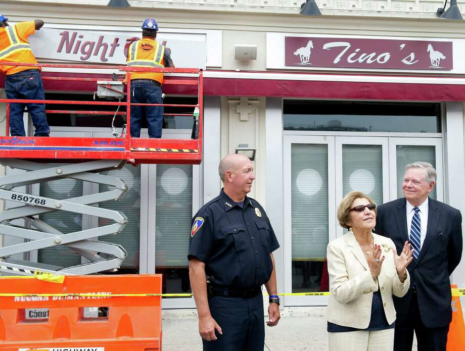 Workers remove the signs from Tino's at 84 West Park Place in Stamford, Conn., on Tuesday, July 15, 2014, as Stamford Police Chief Jon Fontneau, far left, DSSD Executive Director Sandy Goldstein, center, and Mayor David Martin, right, speak. The nightclub's owners voluntarily shut the business down after five people were shot outside early morning Sunday, July 13. Photo: Lindsay Perry / Stamford Advocate