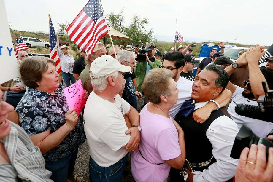 Anti- and pro-immigration activists face off during a protest in anticipation of buses carrying immigrants who are to be housed at a facility in Oracle, Ariz. Photo: Sandy Huffaker, Getty Images