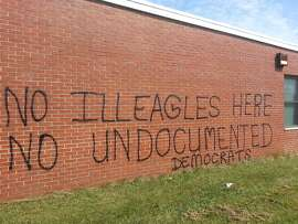 This July 14, 2014 photo shows graffiti on the side of a former Army Reserve Center in Westminster, Md. The U.S. Department of Health and Human Services considered using the building for children who cross the U.S.-Mexico border illegally, but told local officials Saturday they had dropped the idea. The Maryland State Police are investigating the graffiti, which was painted Saturday night or early Sunday, as a hate crime. (AP Photo/The Carroll County Times, Christian Alexandersen)