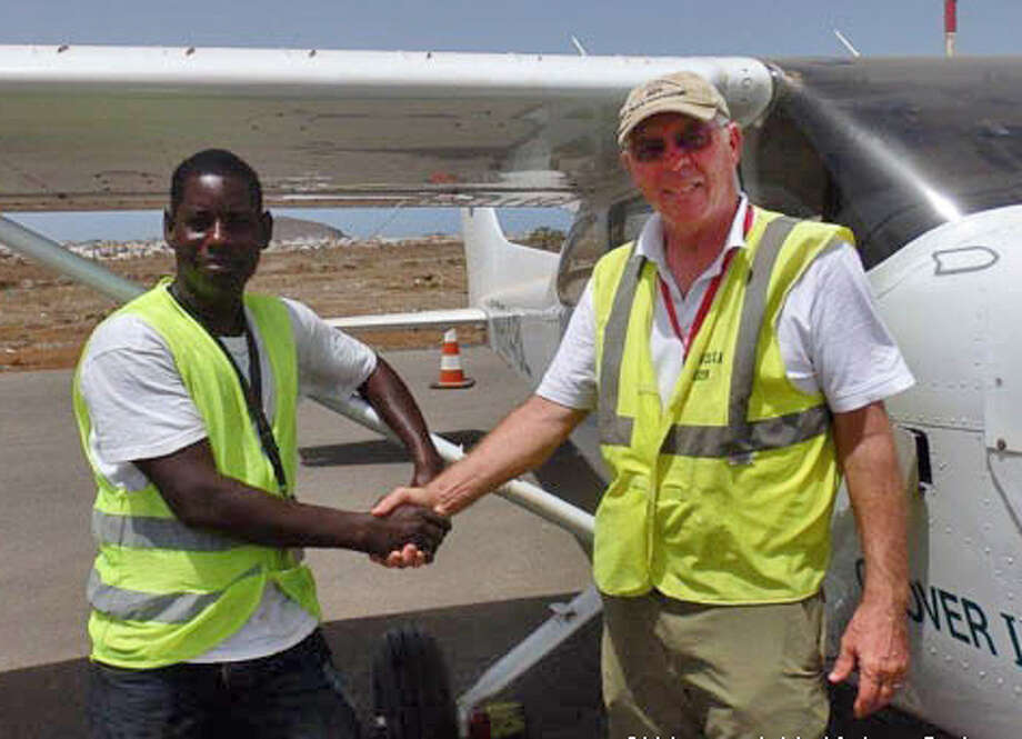 African Parks'pilot Bill Fitzpatrick (right) with an aviation official before departing from Dakar in Senegal on June 19, 2014 en route to the Republic of Congo. Fitzpatrick has gone missing en route between Nigeria and Cameroon. Photo: Contributed Photo, Courtesy African Parks / The News-Times Contributed