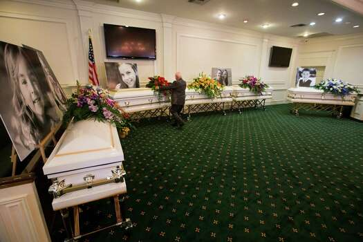 Funeral Director J.D. Baugus adjusts the flowers on one of six caskets of the Stay family before visitation at Klein Funeral Home Tuesday, July 15, 2014, in Houston. Photo: Brett Coomer, Houston Chronicle / © 2014 Houston Chronicle