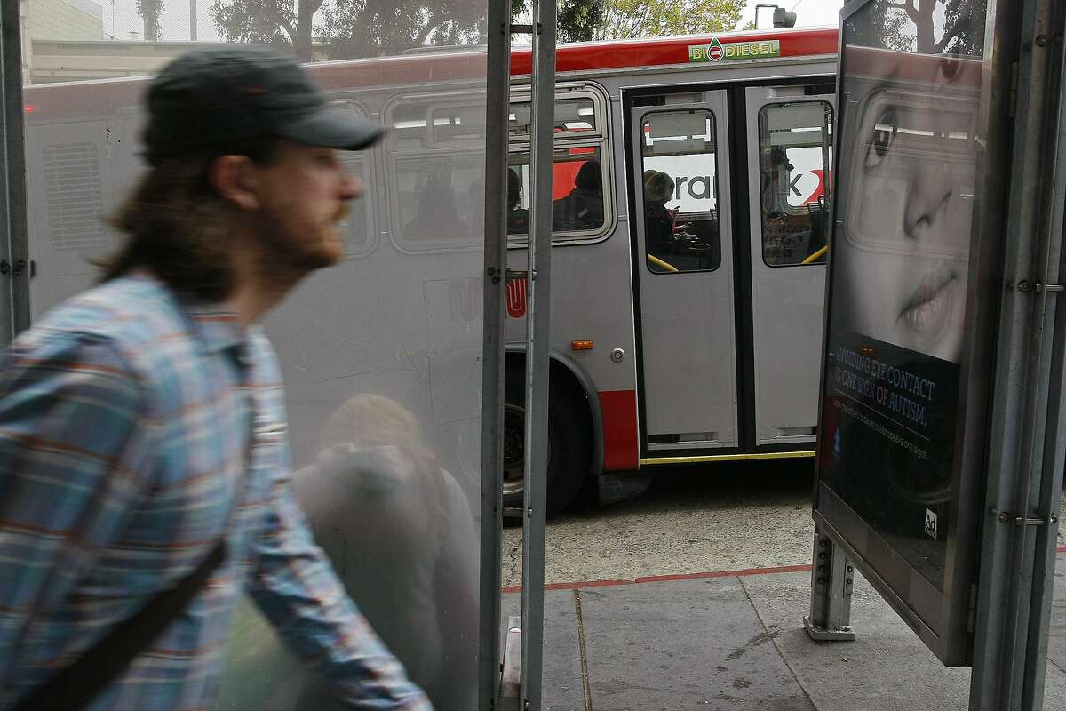 A man passes a bus stop near the corner of Van Ness and Pacific Ave. on Tuesday, July 15, 2014 in San Francisco, Calif. Plans to create level-boarding platforms at bus stops along Van Ness have been cut because they are too expensive to maintain.