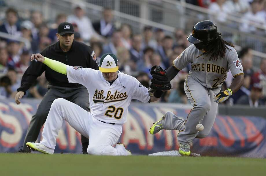 National League outfielder Andrew McCutchen, of the Pittsburgh Pirates, steals third base as American League Josh Donaldson, of the Oakland Athletics, tries to make the tag during the first inning. Photo: Jeff Roberson, Associated Press