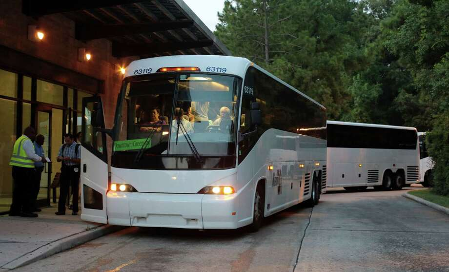 Early morning commuters get on buses Monday at the Research Park and Ride 3900 Marsico Place in The Woodlands. Photo: Billy Smith II, Staff / © 2014 Houston Chronicle
