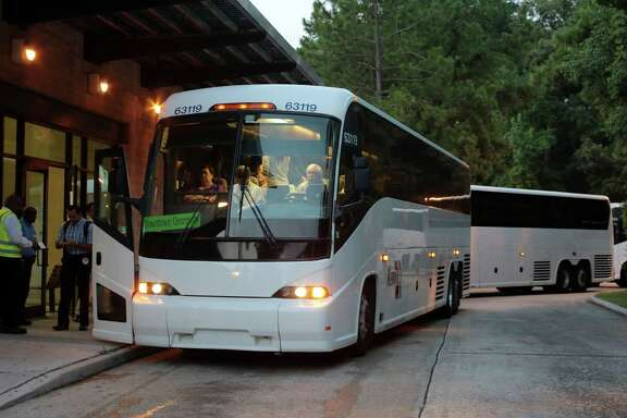 Early morning commuters get on buses Monday at the Research Park and Ride 3900 Marsico Place in The Woodlands.