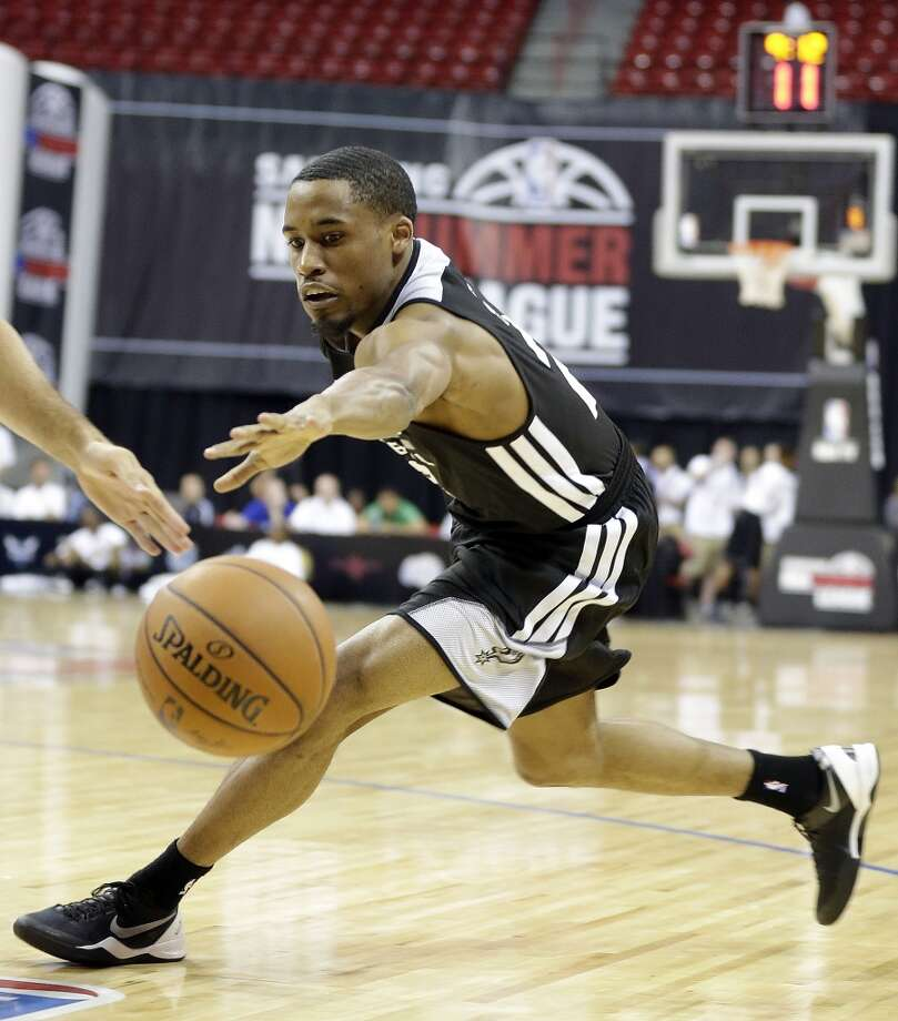 The Spurs' Bryce Cotton reaches for a loose ball during an NBA Summer League game against New Orleans on Monday, July 14, 2014, in Las Vegas. Photo: Isaac Brekken, For The San Antonio Express-News