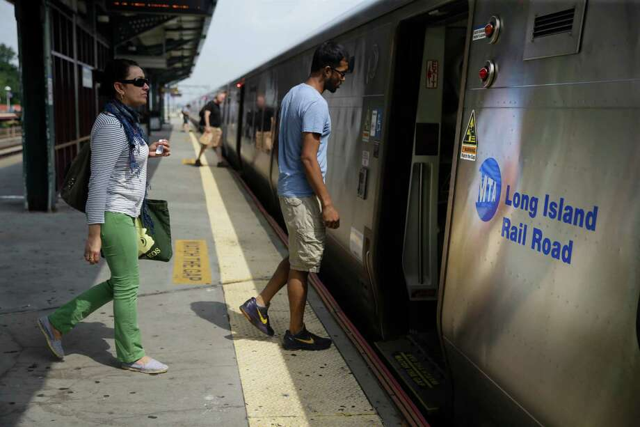 Passengers board a Long Island Railroad train at the Woodside stop in the Queens borough of New York, Tuesday, July 15, 2014. Union negotiators said Monday that weekend talks had collapsed amid a dispute over whether future Long Island Rail Road employees should be required to contribute to their health insurance and pensions. (AP Photo/Seth Wenig) ORG XMIT: NYSW107 Photo: Seth Wenig / AP