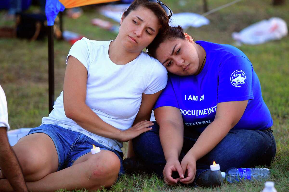 Xochitl Hinojosa rests her head on Sarah Chavez during a vigil to support immigration issues on the border and after Jose Antonio Vargas, Pulitzer Prize-winning journalist and an activist for immigrants, was arrested Tuesday July 15, 2014 in McAllen. Photo by Gabe Hernandez