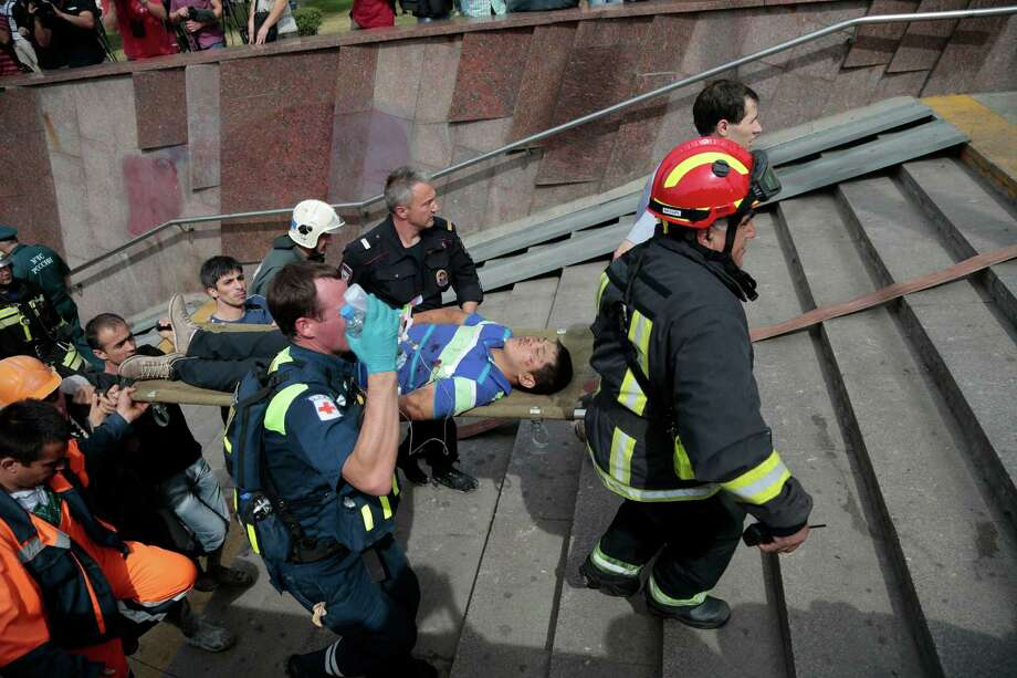 CAPTION CORRECTION REMOVES REFERENCE TO CAUSE OF DERAILMENT. THE CAUSE IS UNDER INVESTIGATION Paramedics, a police officer and a volunteer carry an injured man out from a subway station after a rush-hour subway train derailment in Moscow, Russia, on Tuesday, July 15, 2014. A rush-hour subway train derailed in Moscow Tuesday, killing more than 20 people and injuring scores, emergency officials said. The cause of the derailment is being investigated. (AP Photo/Ivan Sekretarev) ORG XMIT: XAZ106 Photo: Ivan Sekretarev / AP