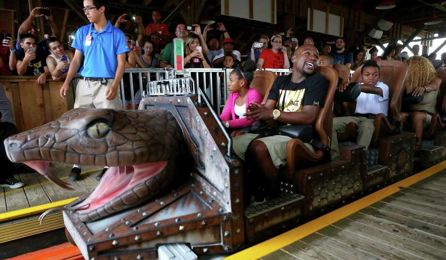 Floyd Mayweather Jr. and his daughter Iyanna have a front-row seat on the Iron Rattler roller coaster before Tuesday's news conference at Six Flags Fiesta Texas to hype his next fight. Photo: Photos By Timothy Tai / San Antonio Express-News / © 2014 San Antonio Express-News