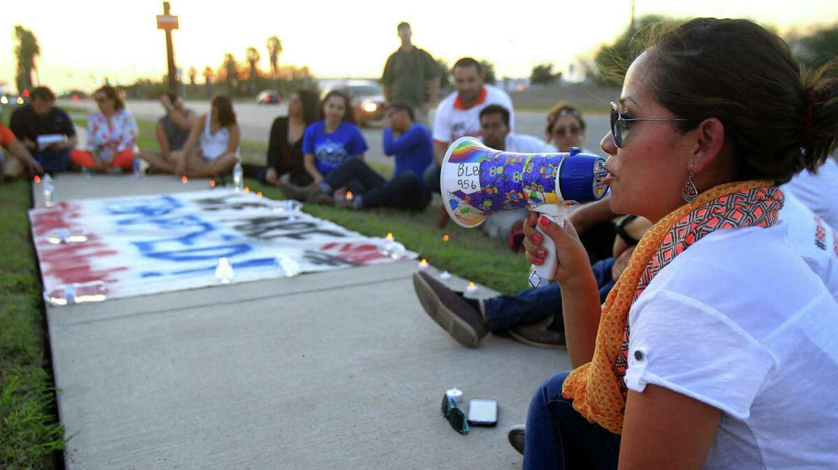 Lupita Lopez uses a bullhorn to tell her story during a vigil in support of immigration reforms on the border.